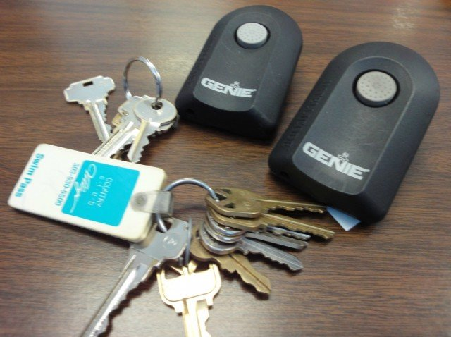 Keys, swimming pool card, two garage door openers on a table top