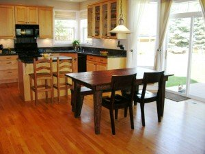 a staged eat-in kitchen with a wooden dining room table in foreground, slab granite countertops and an island