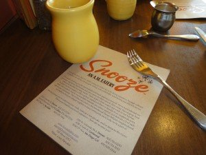 Breakfast menu, coffee cup and spoon on a table at Snooze