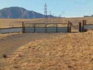 across golden fields a trail leads to a gate and in the background, The Rocky Mountains in Superior, Colorado