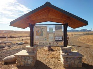 Kiosk, with a stone foundation and trail maps on a board. In the background are the stunning blue skies of the Rocky Mountains