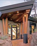The grand front entyway to a mountain home, with colorful leaded glass doorway and overhanging archway entry