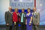 five Realtors in front of the Realtor Logo, all dressed up
