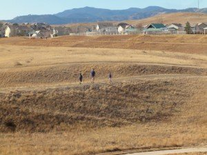 Rock Creek open space; there is a parent and two smaller children walkinga long a path, surrounded by golden rolling fields. In the near background is a housing subdivision and beyond that, the Rocky Mountains