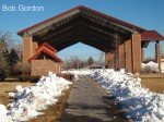 Lined with snow piles, a walk way leads to a large outdoor building. The roof must be 5 or 6 stories high