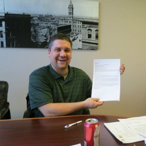 in a Boulder real estate closing Chris poses with deed of trust
