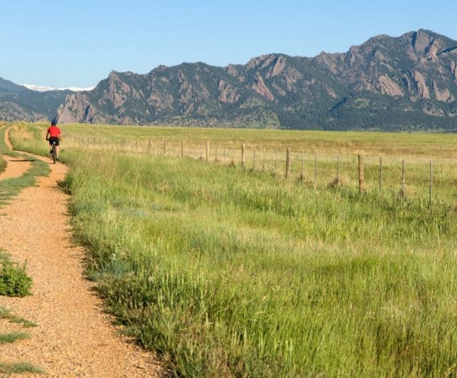 cyclist on trail along boulder open space with view of the flatirons in distance