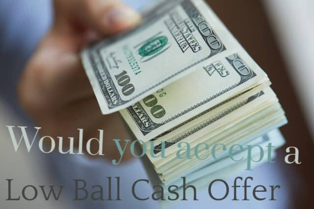 hand offering a cash low ball offer offer of hundreds of dollars