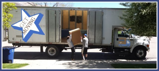 looking from a home, down the driveway and into the open bay of a moving truck as two movers start to load a van