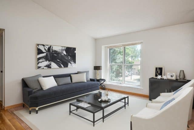 virtual staged space at 131 s madison with a black couch and glass table and black and white picture on the wall