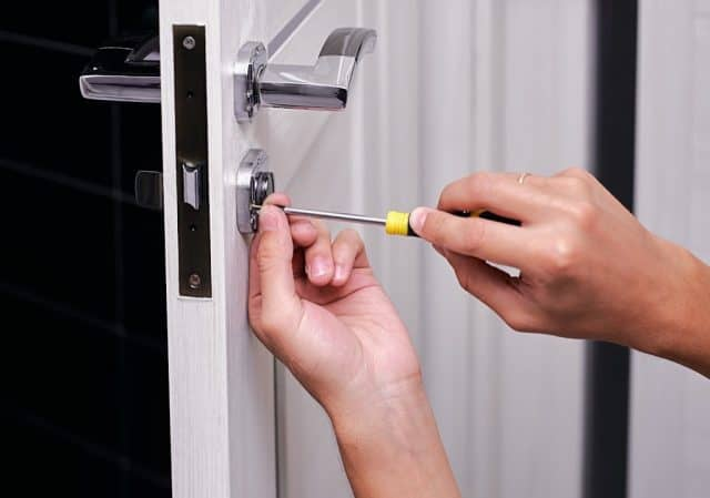 hands with screw driver changing the lock on the door of a boulder listing coming up for sale