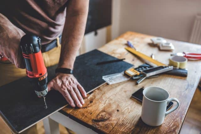 man making quick cheap home improvements drilling a board braced on a table with a cup of coffee and various tools strewn about