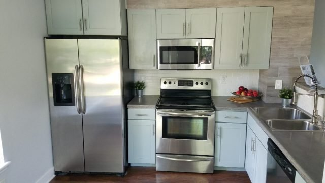 stainless steel appliances and concrete counters in remodeled condo kitchen