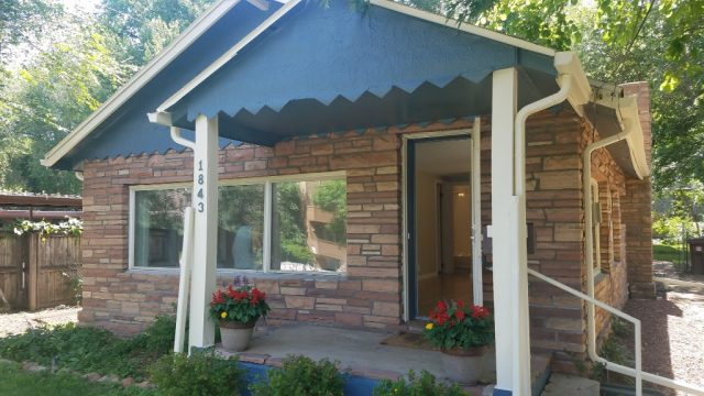 brick and siding bungalow at 1843 23rd street with a blue bird blue covered patio in front f stone and brick facade