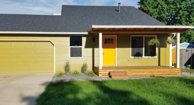 exterior view 214 s jefferson louisville co house is off yellow with a bright yellow door and wood covered deck