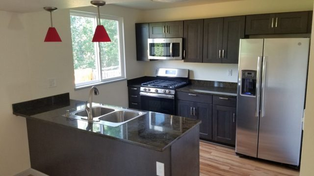 remodeled kitchen with stainless steel appliances and coffee colored cabinetry plus a dark slab granite counter
