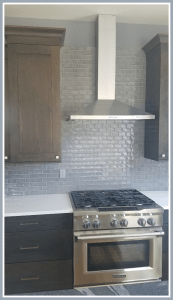 view of cabinets split by a range hood and stainless steel range oven in the background is blue tinged glass tile and two different counters are visible