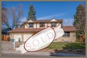 12223 w 68th avenue arvada co exterior home shot with the word sold across the front