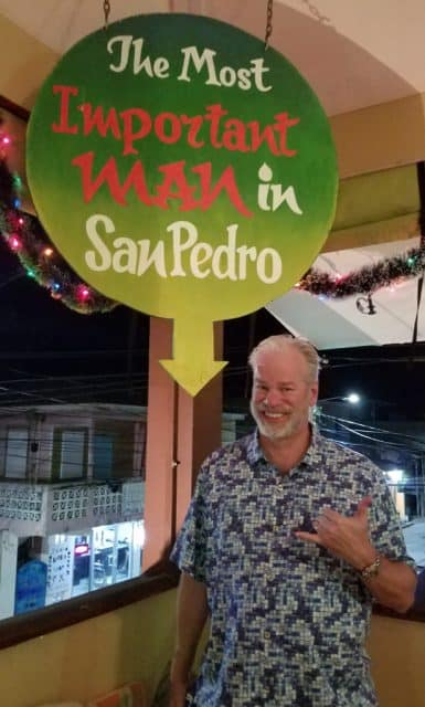 boulder real estate agent bob gordon posing by sign that reads the most important man in san pedro taken at a restaurant in belize