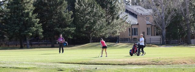 woman in pink tees off at boulder country club lifestyle of living along a golf course is alluring to many in area