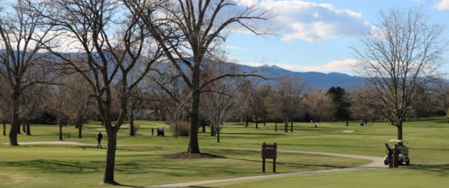 looking west at the colorado rockies across a golf country club course in boulder with a few players out in the late afternoon light