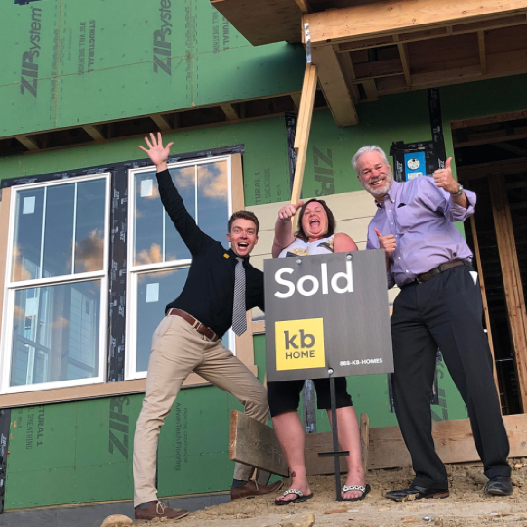 kb homes sales guy plus home buyer and her realtor bob gordon all very excited in front of an under construction home the day home buyer went under contract