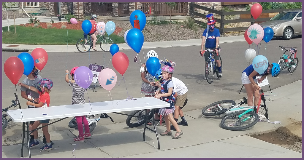 kids getting balloons and decorating bikes for the 4th of july in trails at coal creek