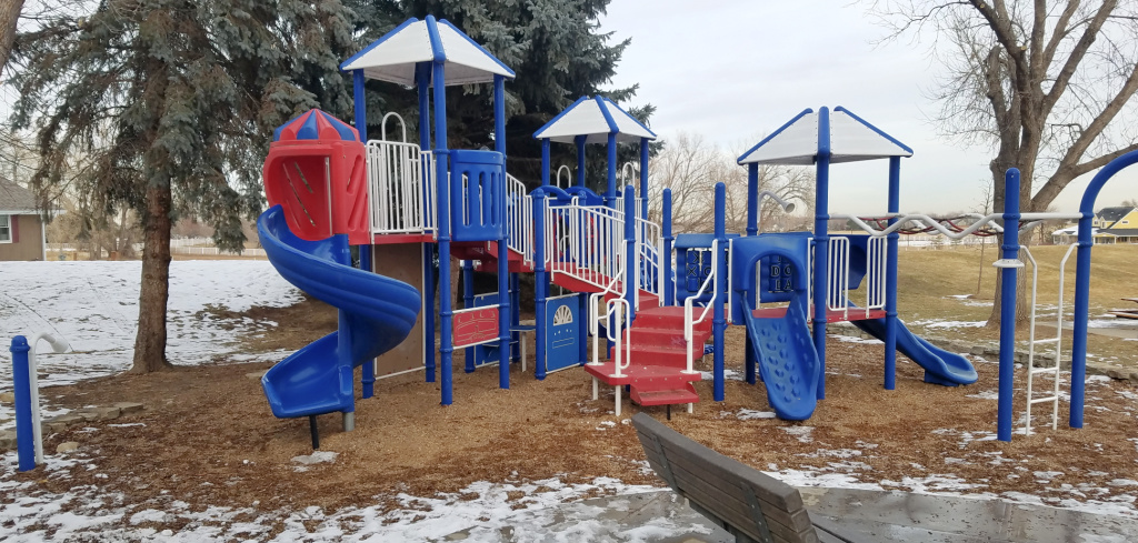 beacon hill playground with red steps, blue slides, covered areas and plenty of space to run around