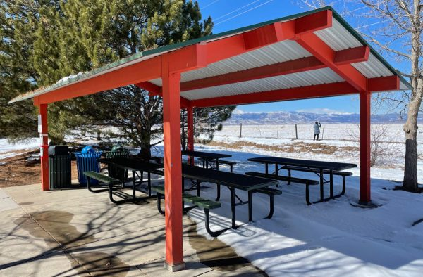 annette a brand picnic shelter is bright red with tables and a fabulous view of mountains and there is one person walking in the background