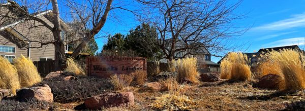 landscaping wiht a red brick wall and the words waneka landing while deep blue skies overhead