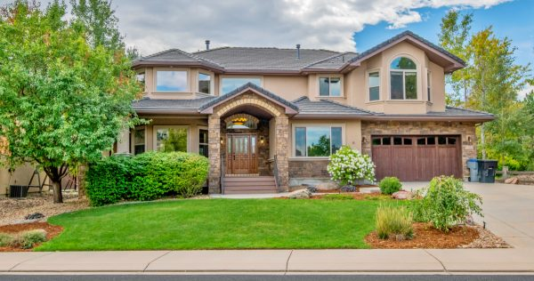 a beautiful two story stucco house with green lawn and landscaping under partially cloudy skies