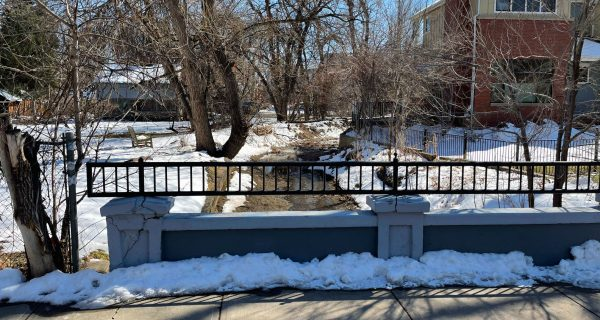standing on a small bridge looking out at a creek running through the whittier neighborhood in boulder co